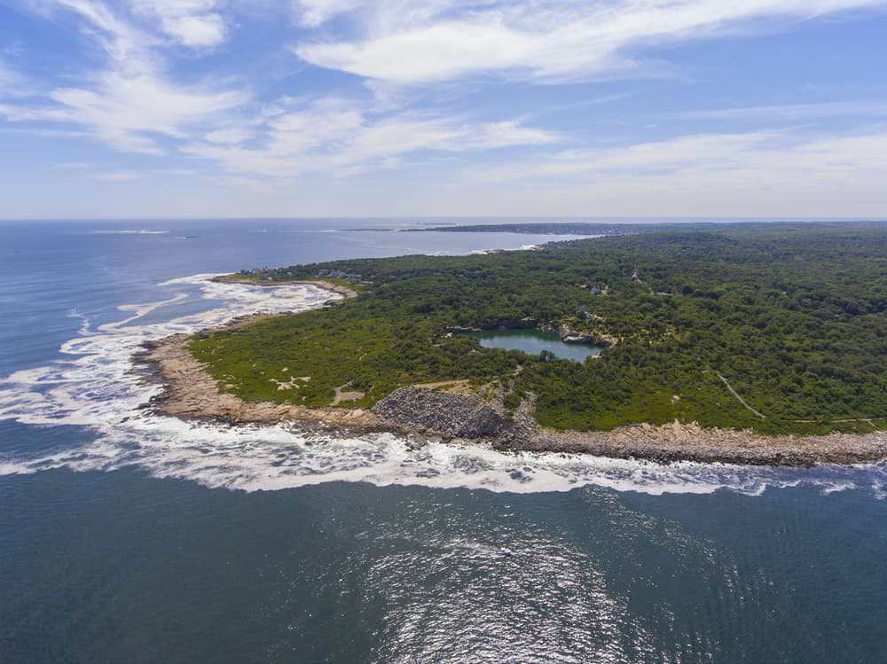 A drone view of Halibut Point State Park on the coast of massachusetts: a green island surrounded by rocky shore