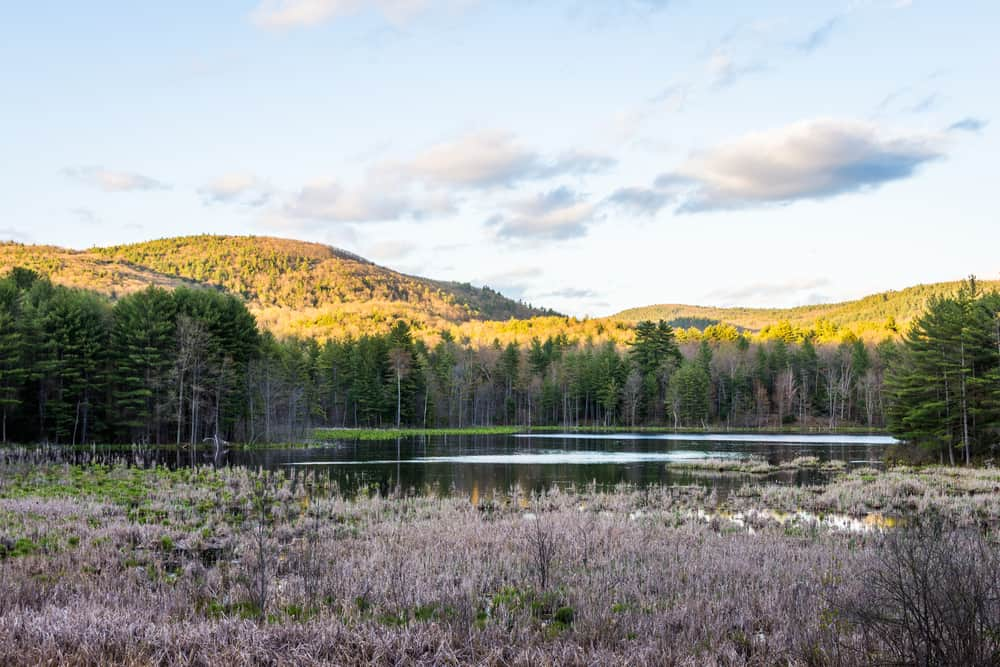 things to do in keene nh - low mountain bathed in sunlight with a calm lake in front