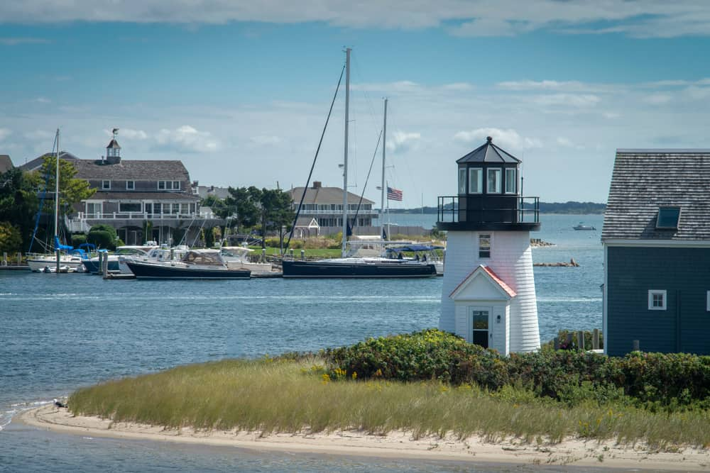 A view of a light-house, few boats and houses by the bay, Cape cod Mass