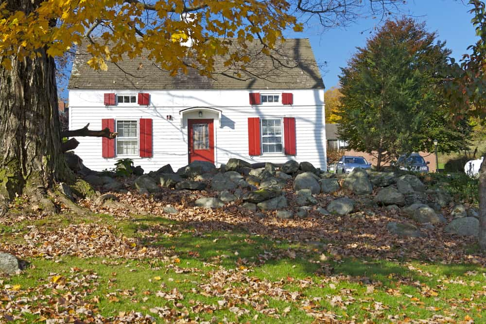 A picture of a white house with red shutters behind a stone wall and a maple tree with yellow leaves