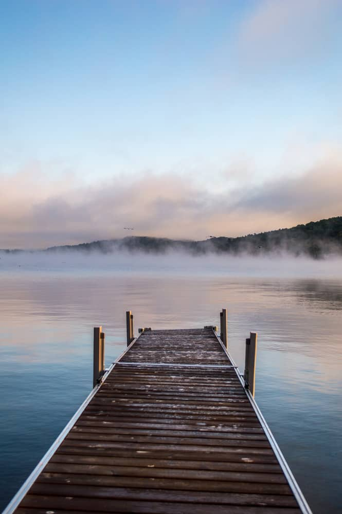 sunrise over Lake Bomoseen, a misty lake at the end of a brown wooden dock