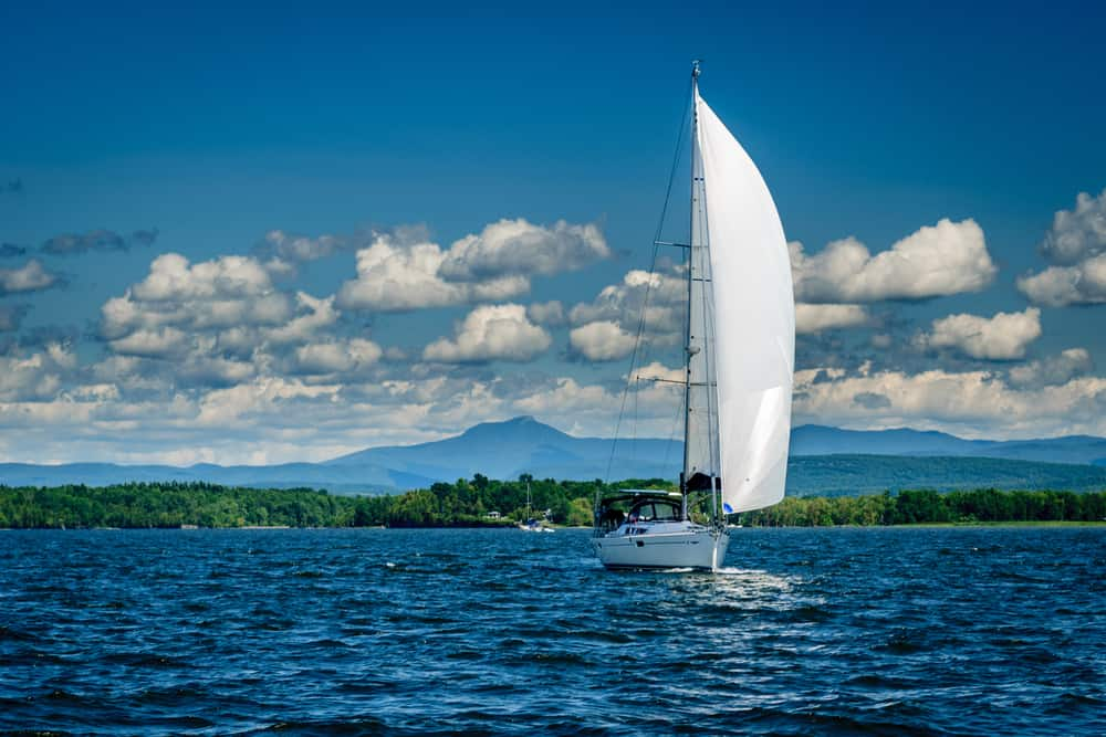 a clear blue sky and the blue lake with a white sail boat