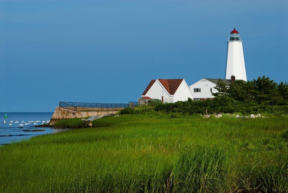 A picture of a white and red lighthouse by the sea-side called the Lynde Point lighthouse, one of the most beautiful places in CT