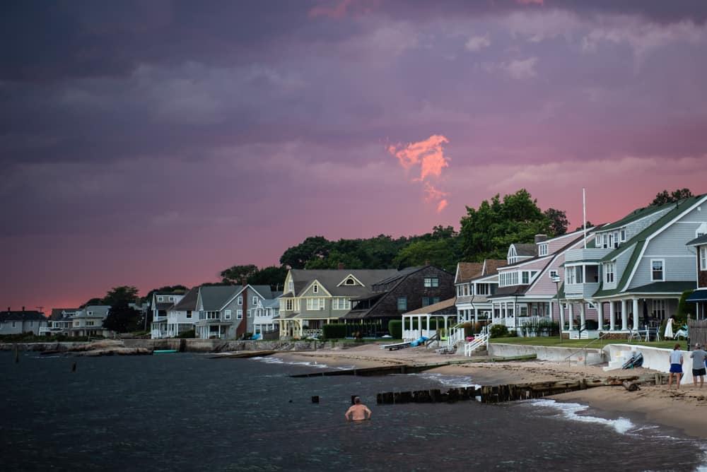 a dark purple sunset or possible storm cloud hovers over coastal houses by the shore of CT