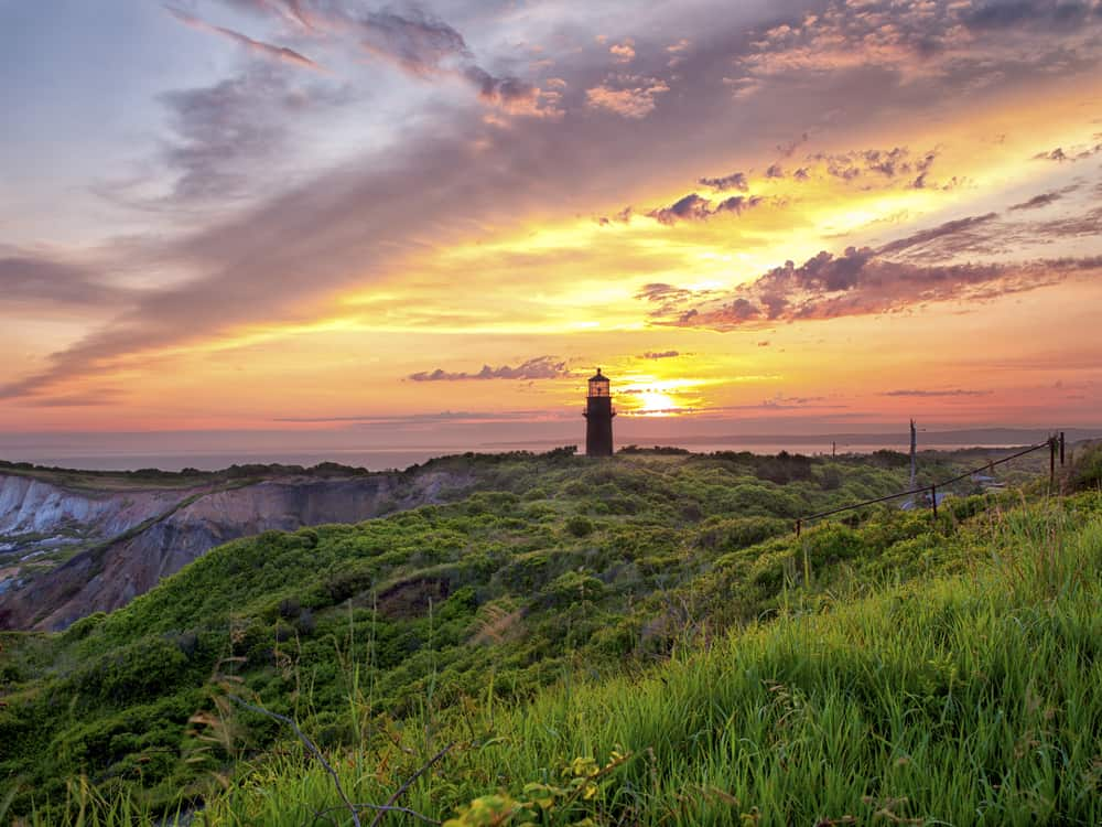 A sunset view of a lighthouse on a grassy stretch in Marthas Vineyard, the sea is in the distance