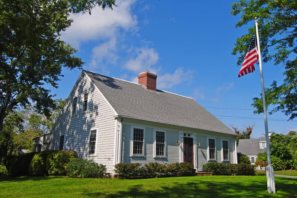 A pole with the flag of United States in front of a grey house in New England