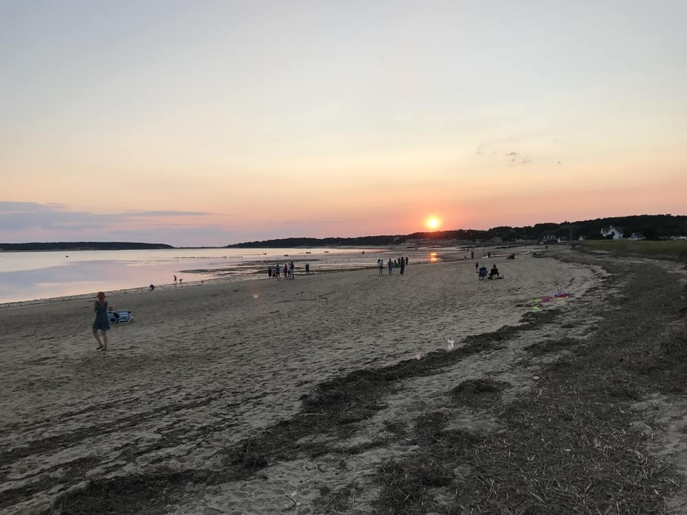 sunset in the distance with a flat grey sandy beach in the foreground