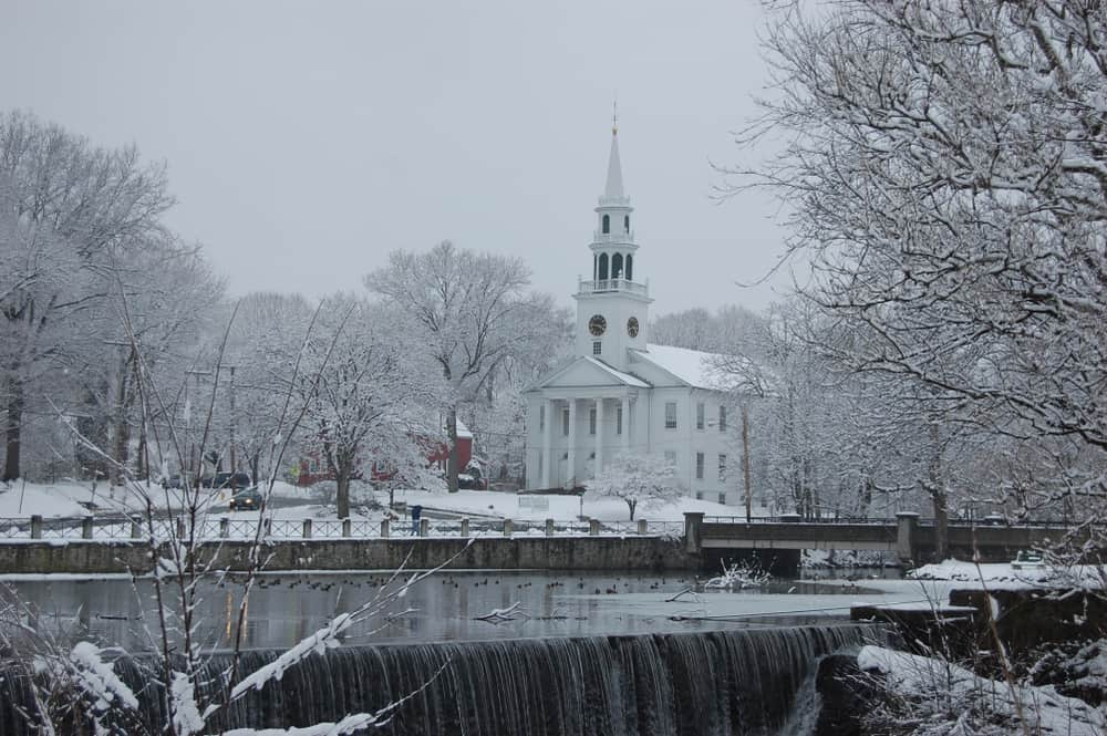 A picture of a snow-clad church behind a small waterfall dam in new england