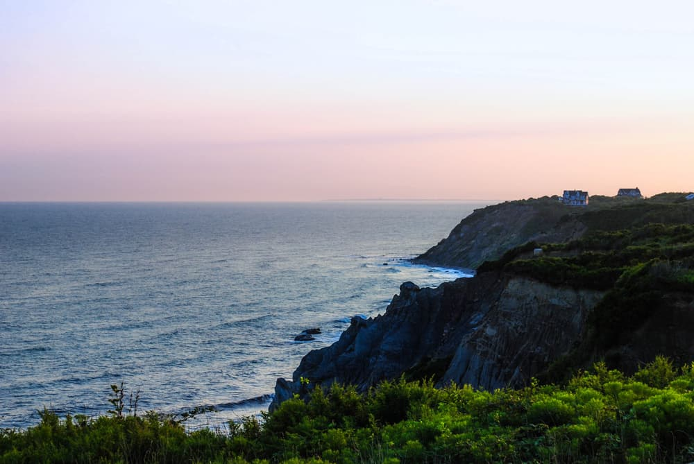 striking cliffs set against the ocean with a small house in the distance, rhode island