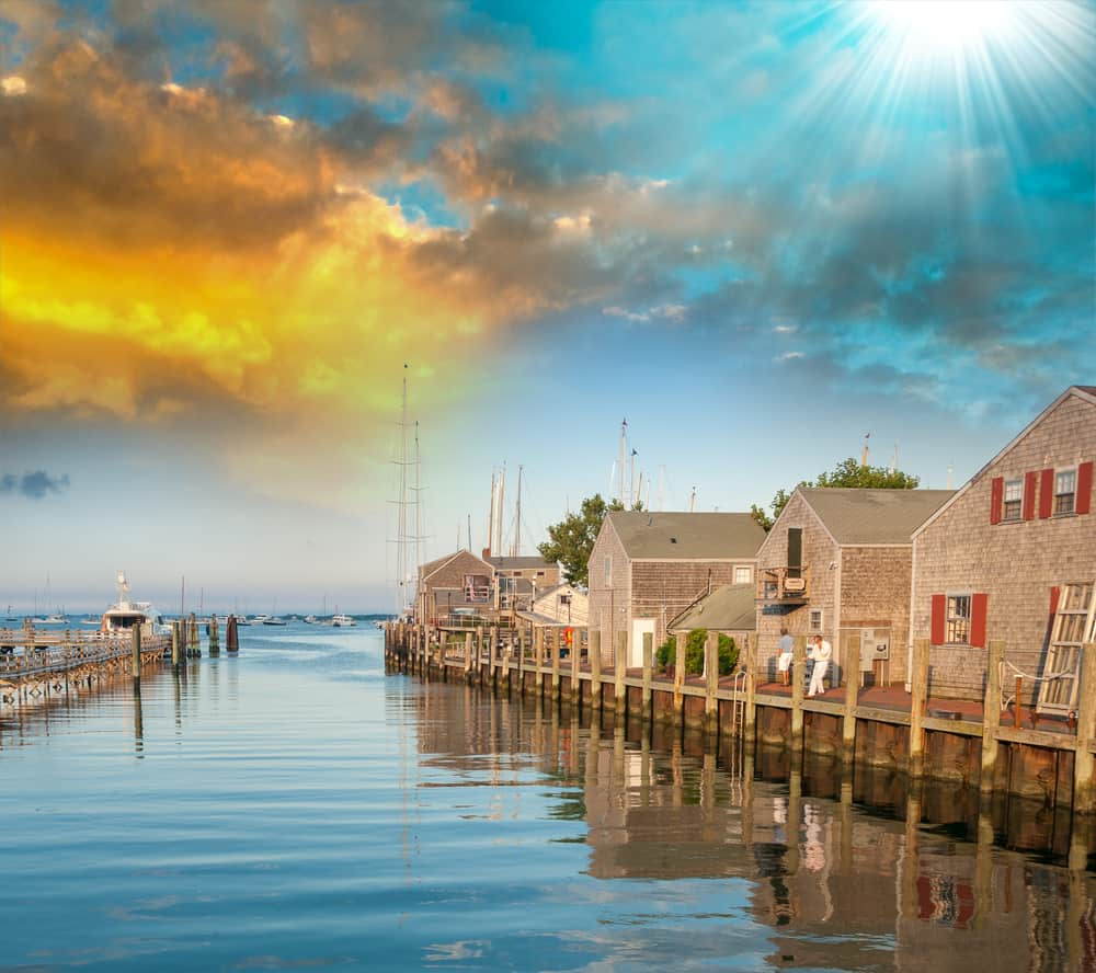 A picture of a row of wooden shingle houses on the seaside in Nantucket, next to a short canal