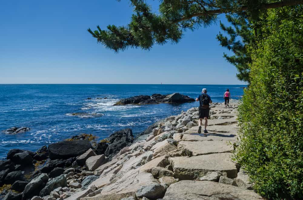 a man and woman walk along a rocky walkway next to the ocean, newport rhode island