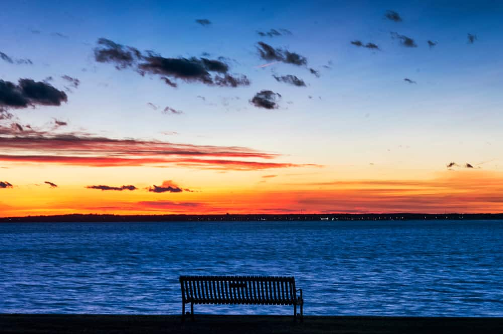 a lonely bench sits in front of still blue water and a distant orange sunset