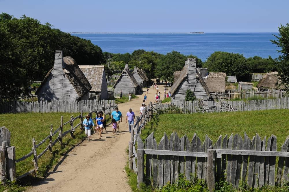visitors walking down a path between early colonial houses, plimoth plantation usa