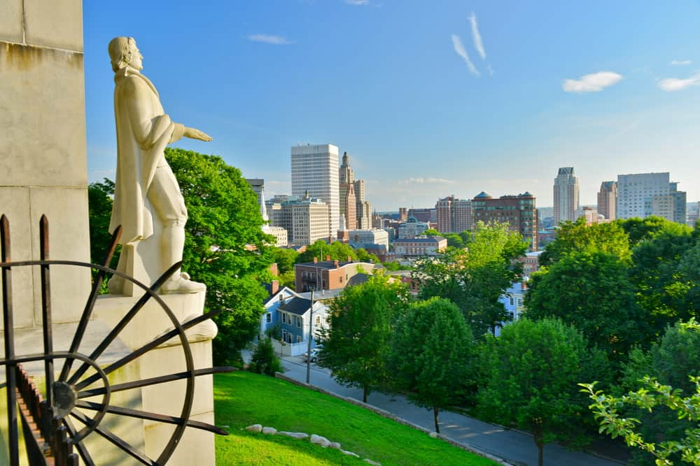 a sunny day over a city skyline with a historic figure statue in the left foreground