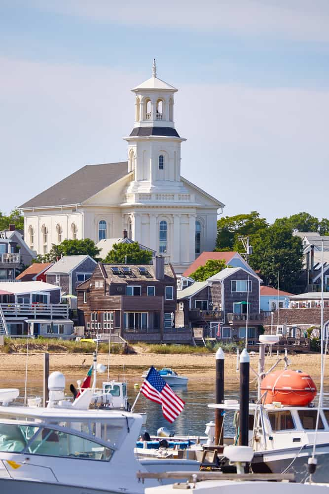 A view of trail of yachts on the shore with a few houses and a church on the other side
