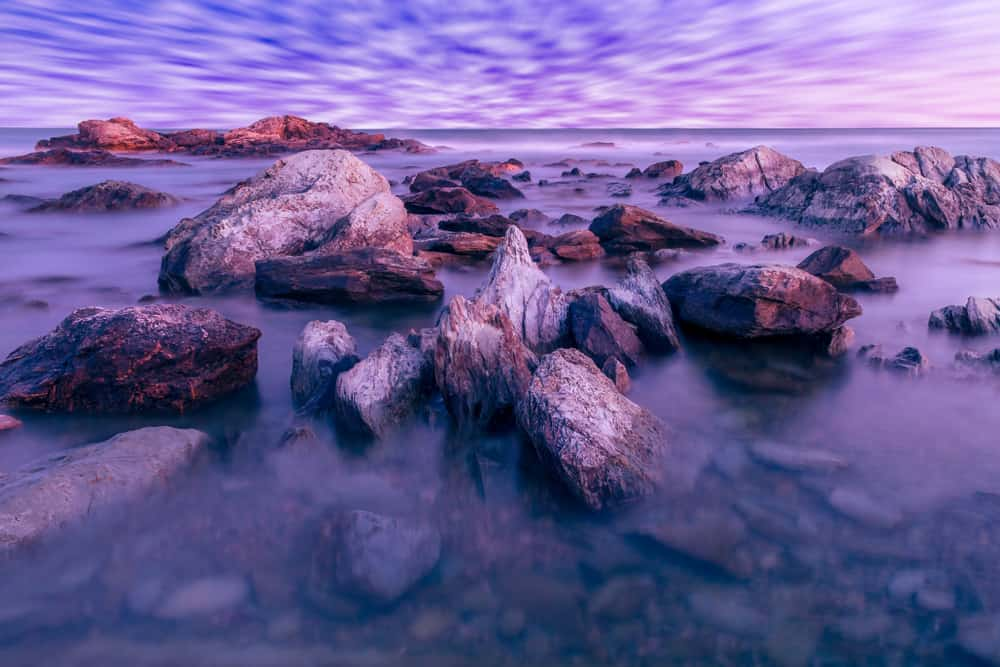 a long exposure closeup shot of rocks in the shallow part of a beach