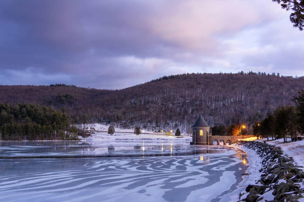 An earthen embankment dam in winter next to a frozen lake