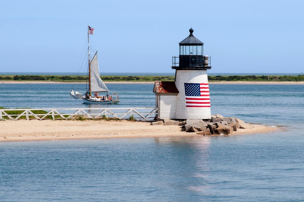 beach towns in massachusetts header - image of short white lighthouse on a calm stretch of sand with an american flag on it. a sailboat goes by in the background