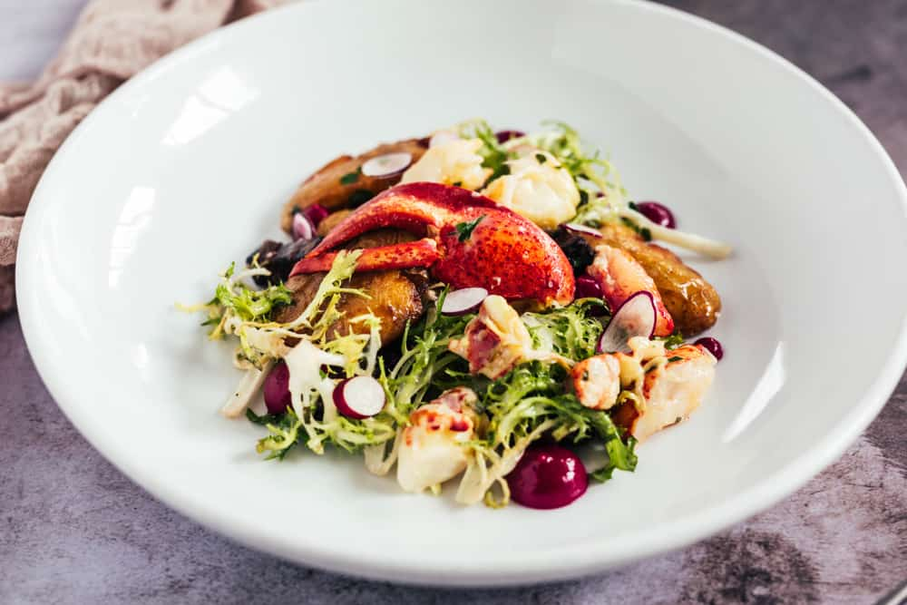 best restaurants in portland maine - image of white plate holding green salad with lobster claw on top