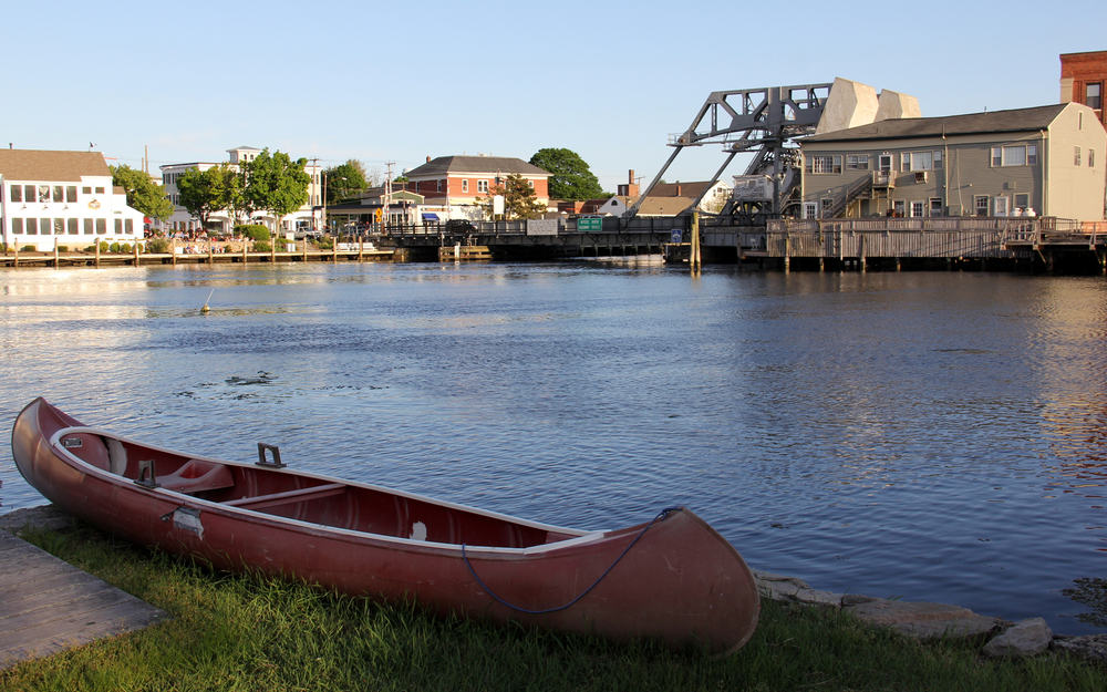 Canoe seating on the grass by the water, Mystic River Bascule Bridge in the background, view at sunset