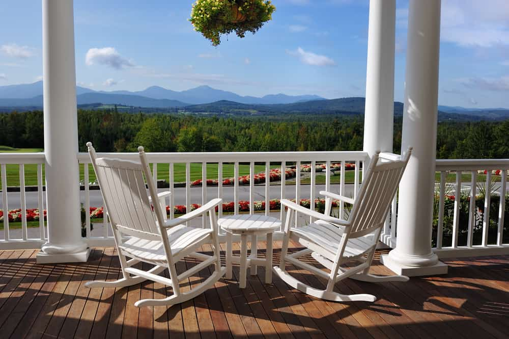 weekend getaways in new hampshire - image of two white rocking chairs on a porch facing green mountains in the distance on a sunny day