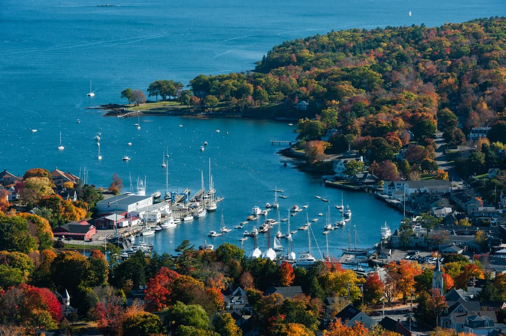 things to do in camden maine - aerial view of ocean bay off the coast of maine, light fall leaves are seen