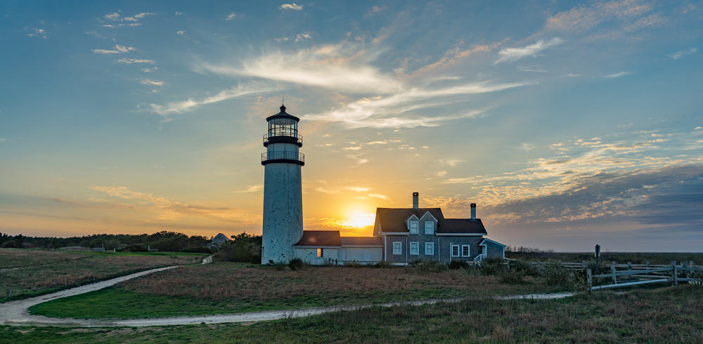 classic new england lighthouse under clear skies with a few wispy clouds