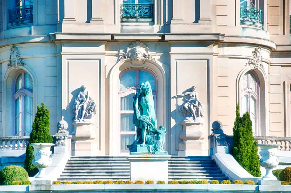 exterior of a luxurious mansion with greek styled statues and a staircase