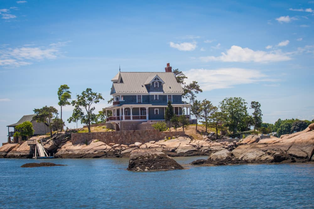 A stunning blue victorian home stands alone on a rocky island on a sunny day