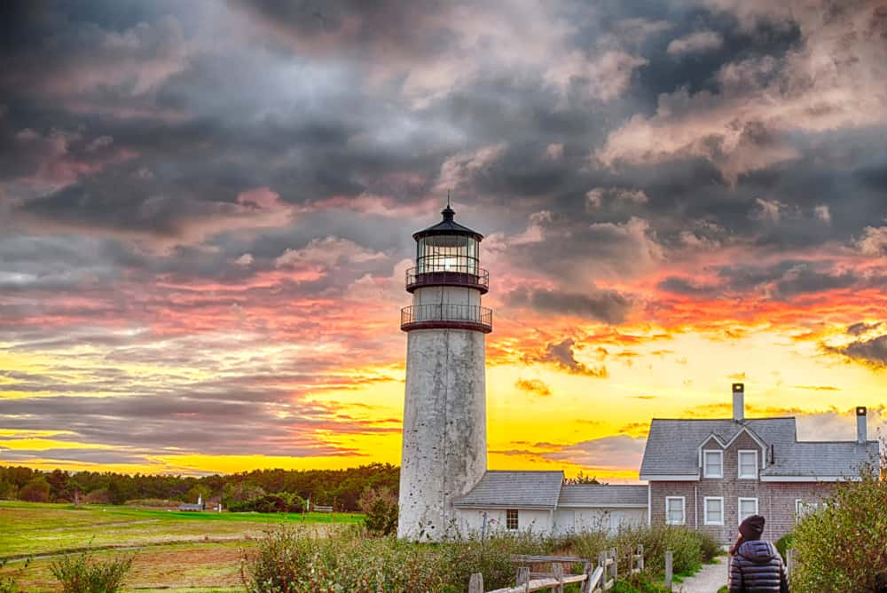 The view of a cloudy sky after rain with a lighthouse and a grey house in Cape Cod