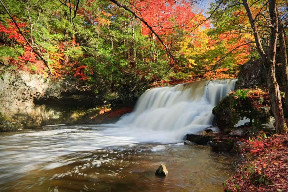 a softly flowing waterfall cascading through fall foliage