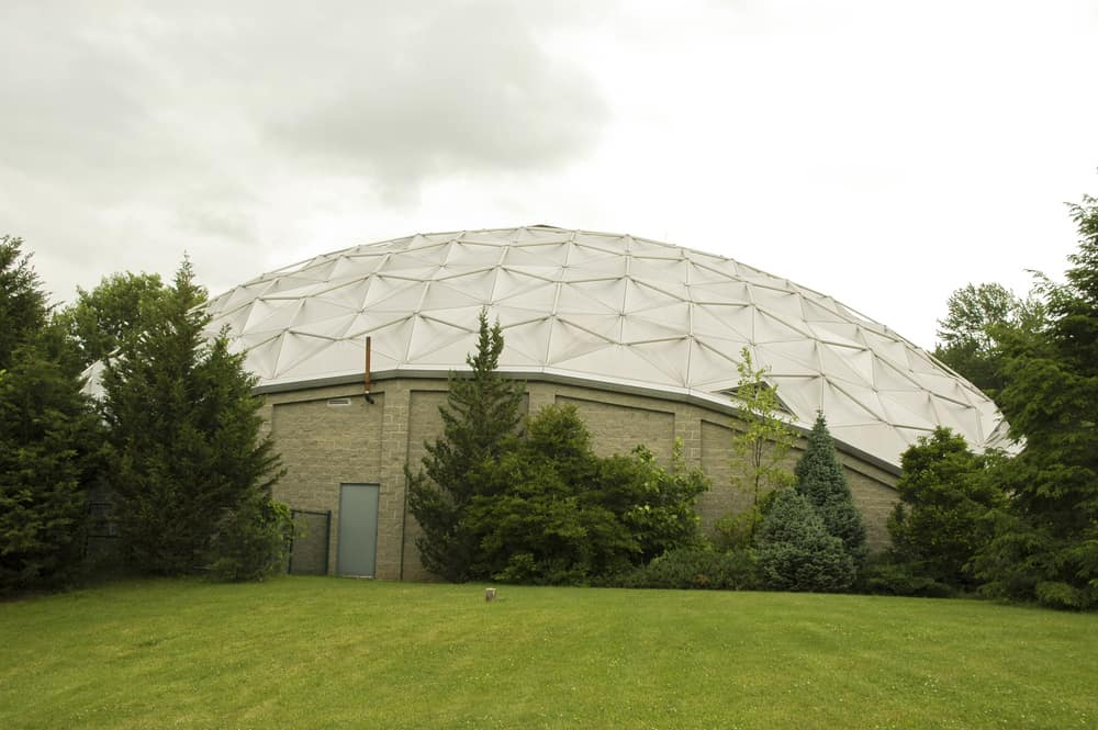 Tan dome shaped building surrounded by trees