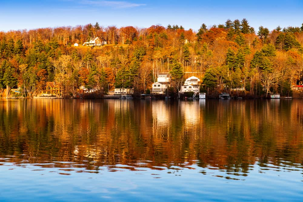 a calm lake in the foreground and a wooded shore in the background. fall foliage surrounds boat docks and lake houses