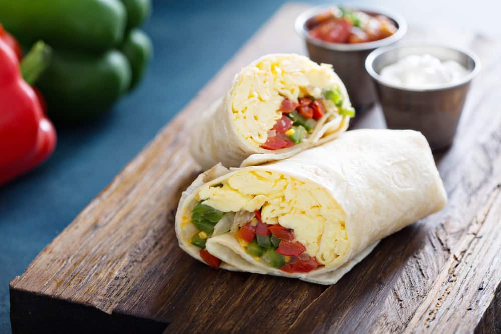 two breakfast burritos filled with eggs and veggies