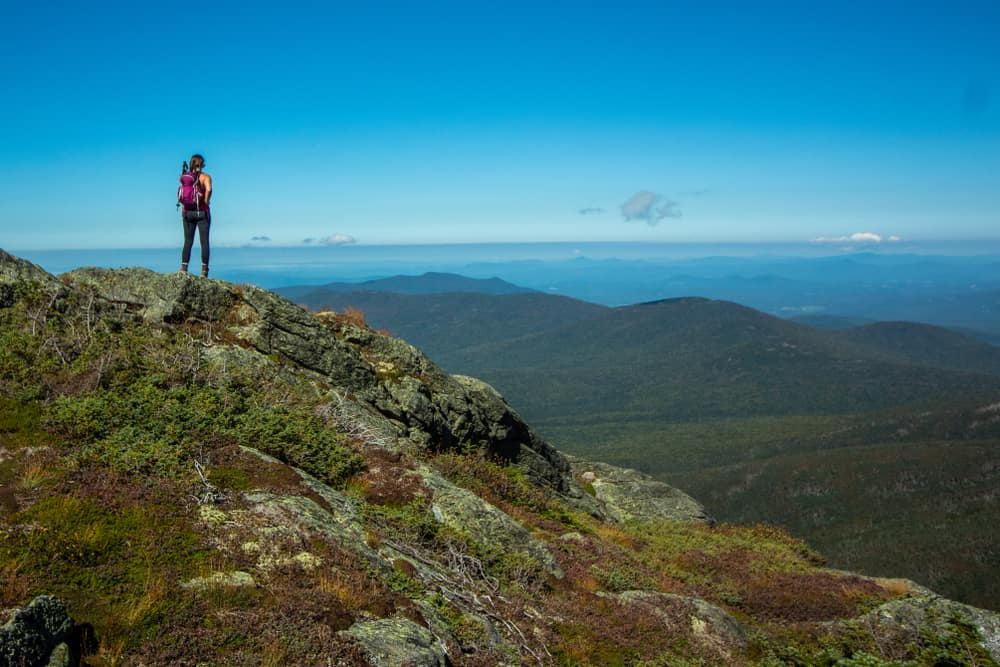 a hiker at the peak of mt washington new hampshire, hazy peaks in distance