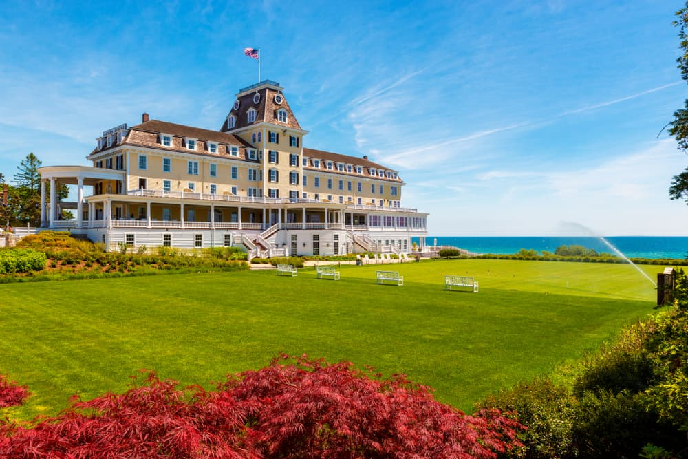 a regal new england mansion hotel is seen near the turquoise water in rhode island