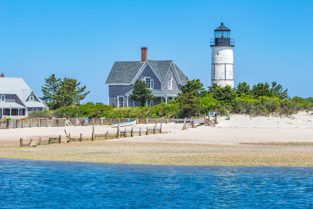 white lighthouse and grey house on beach, things to do in Sandwich Maine