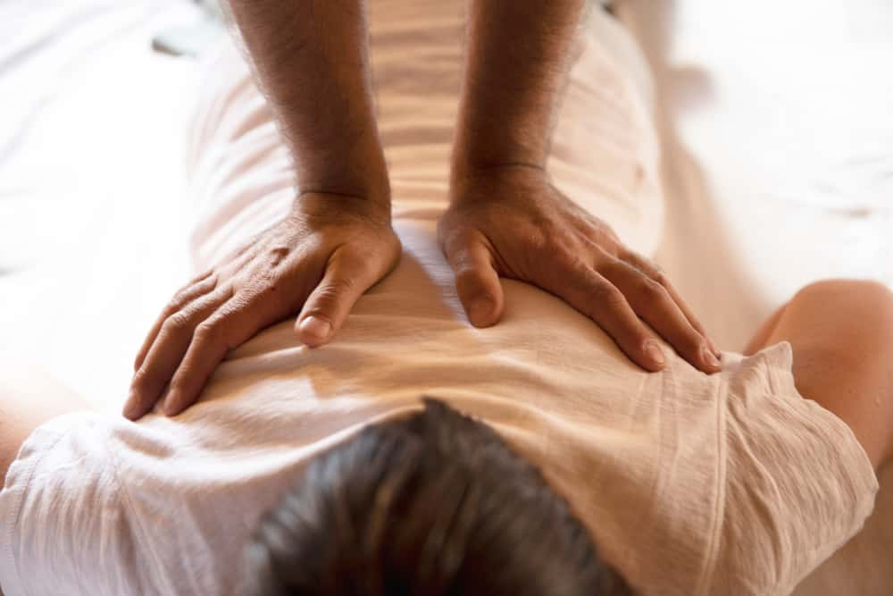 Person getting a massage in a white shirt.