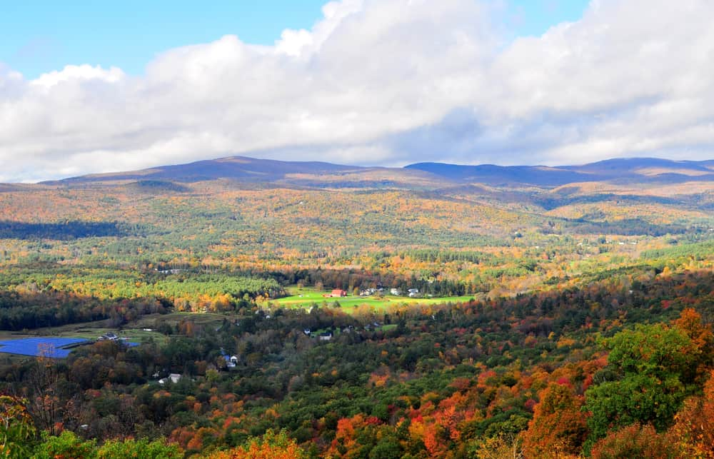 rolling small mountains seen from above, dotted with bright fall foliage