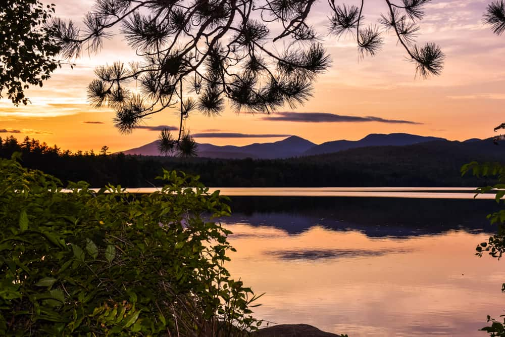 things to do at lake winnipesaukee - a gorgoues sunset seen over new hampshire's most well known lake. mountains in the distance