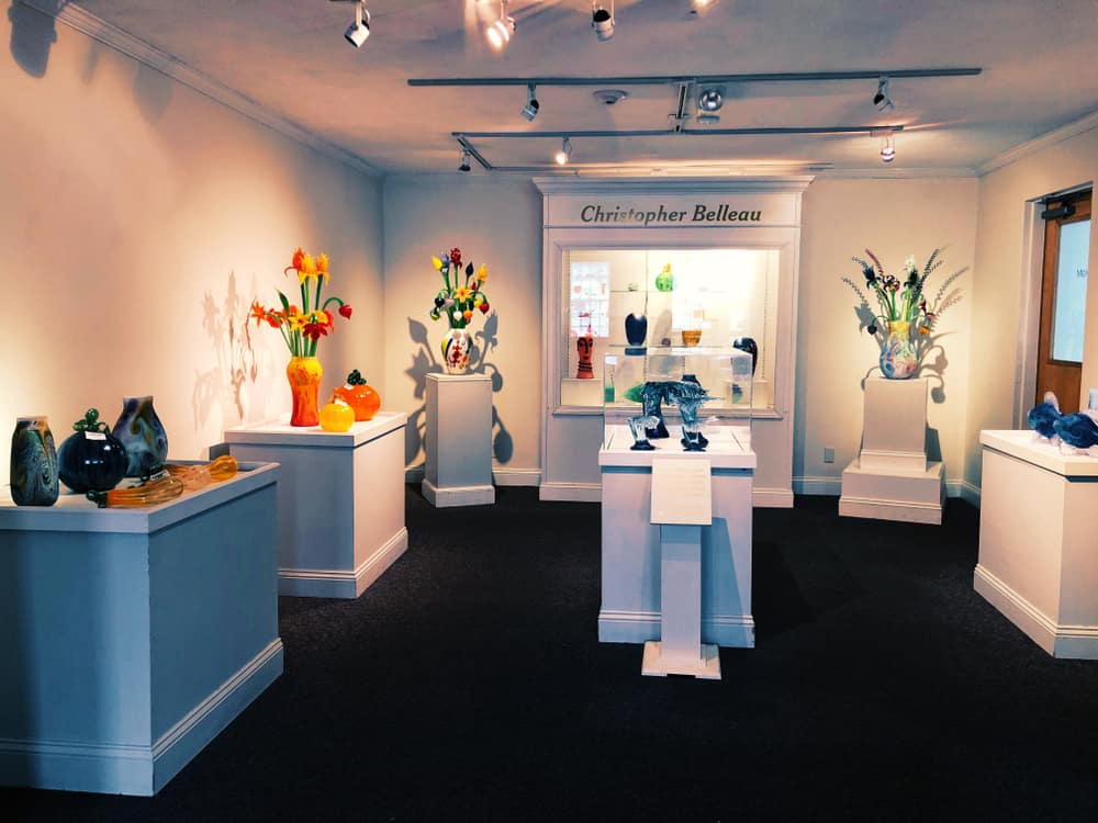 glass art exhibits on white podiums in museum interior