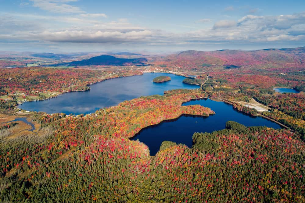 aerial view of a dark blue lake surrounded by fall foliage in the northeast kingdom of vermont