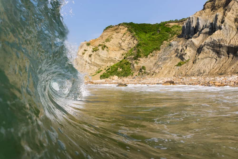 closeup of a wave curling as it moves toward the beach that has dune-like cliffs i