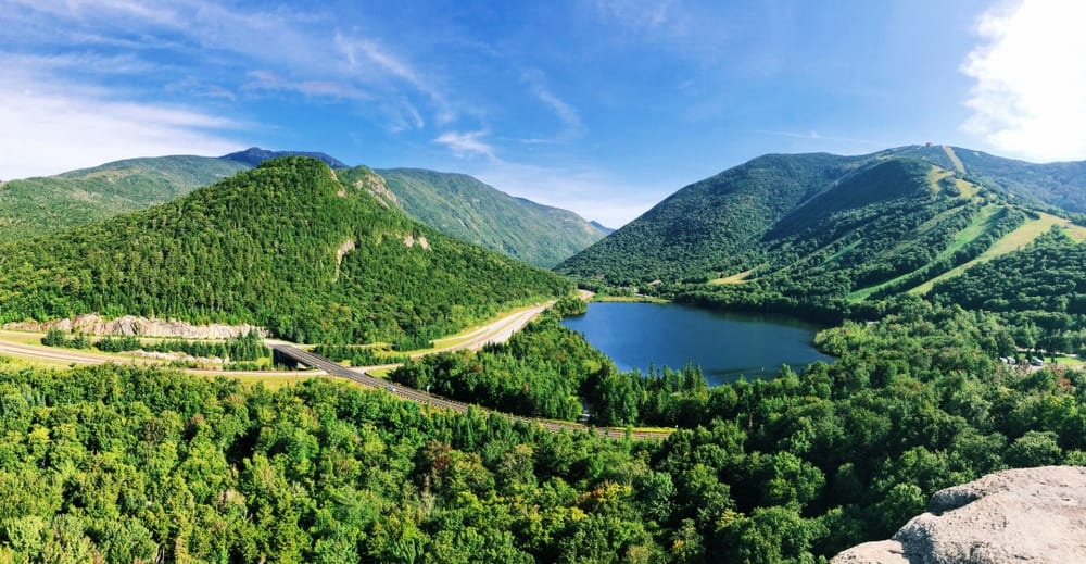 a small blue lake surrounded by emerald green mountains in new hampshire
