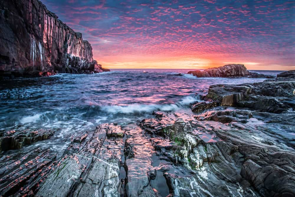 rocky cliff face with waves crashing up against it and a perfect sunset in the sky