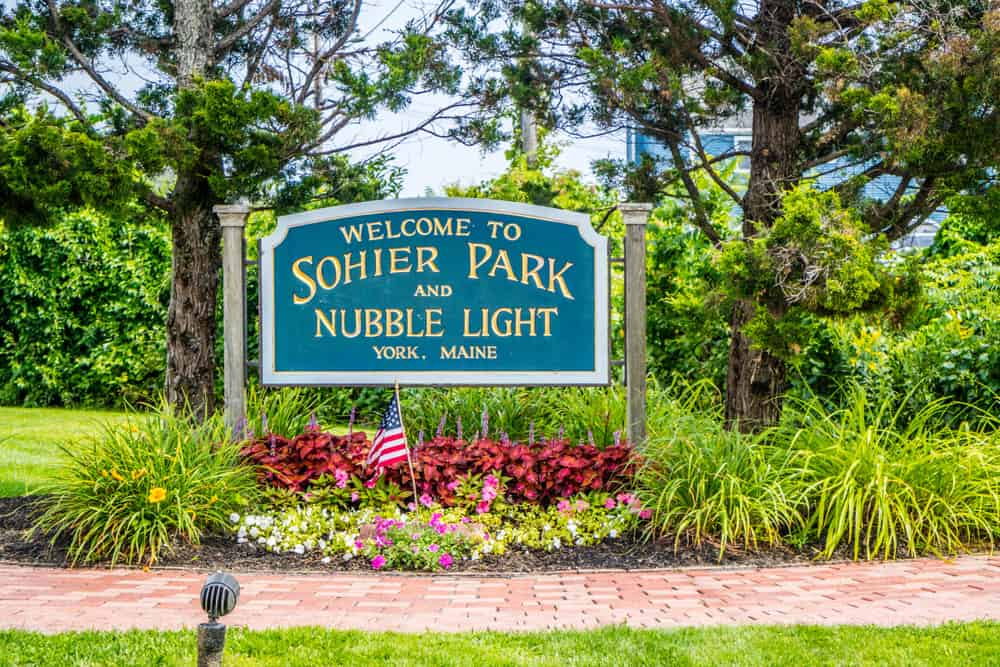 """""""Welcome to Sohier Park and Nubble Light in York, Maine"""" sign surrounded by trees and flowers"""