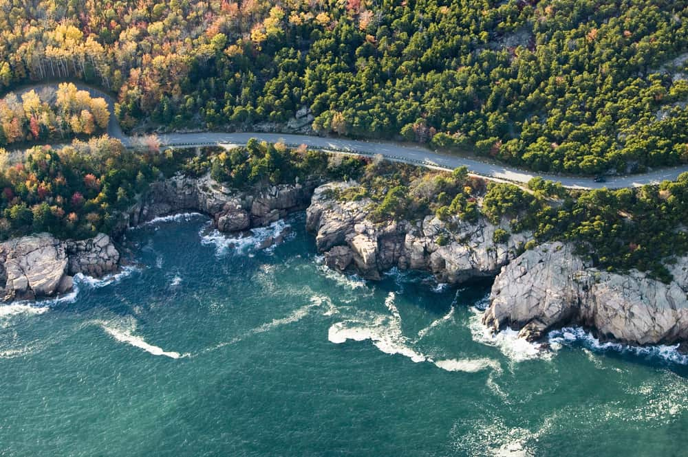 drone shot of a coastal road next to aqua sea and cliffs - boston to acadia national park road trip