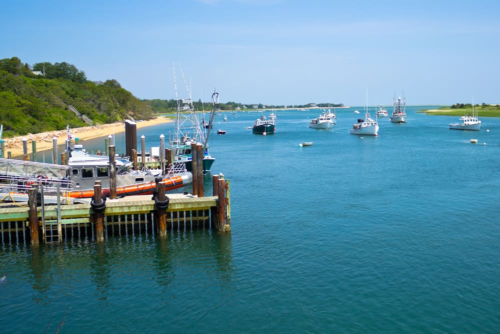 Boats are moored in a bay near the Chatham Fish Pier, MA, on Cape Cod.