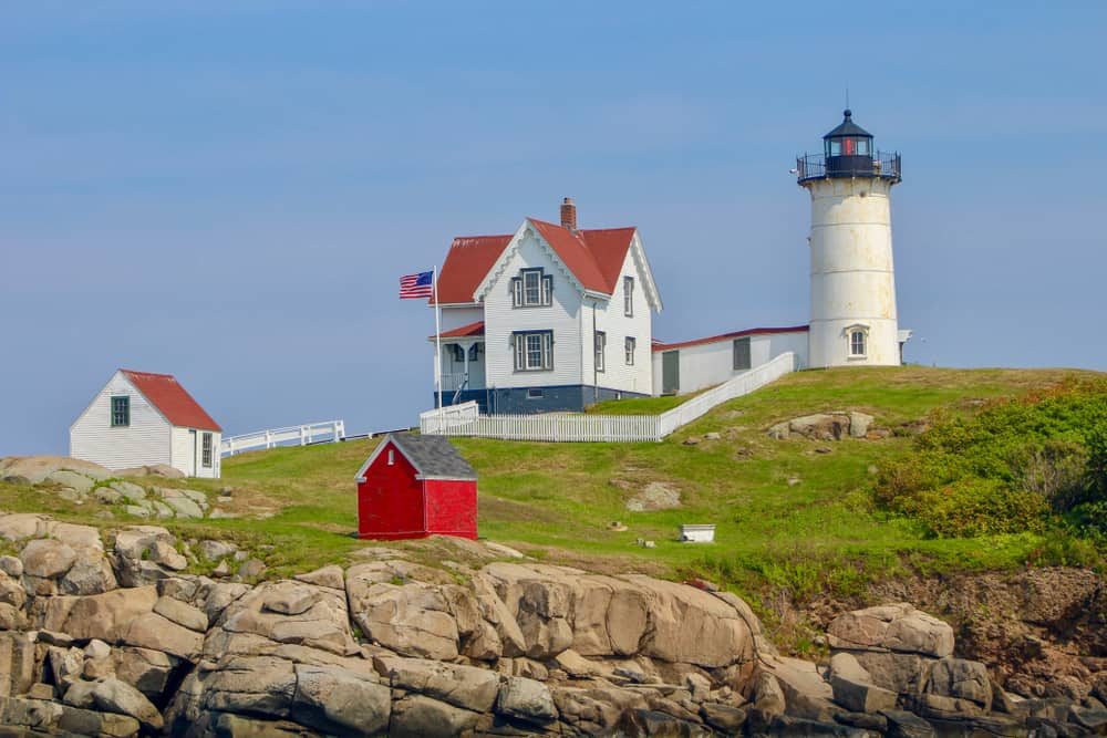White lighthouse on a cliff next to a small home and two sheds under a blue sky