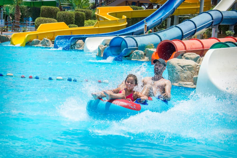 a young girl and a man ride a double inner tube raft out of an enclosed water slide
